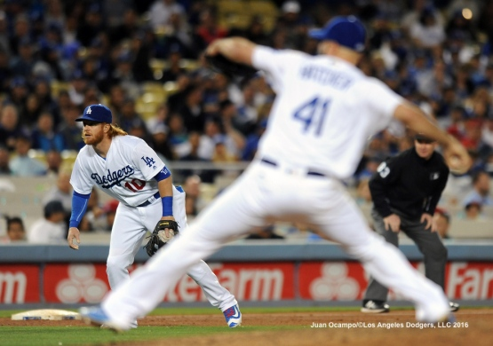 Justin Turner gets ready to cover on a bunt as Dodgers reliever Chris Hatcher throws to the plate.
