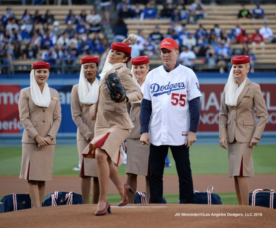 Former Dodger pitcher Orel Hershiser watches on the mound as one of the Emirates Airline attendants throws the ceremonial first pitch prior to the start of the game. Jill Weisleder/Dodgers