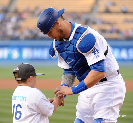 Catcher Yasmani Grandal signs a ball for a young fan during Kids Take the Field. Jill Weisleder/Dodgers