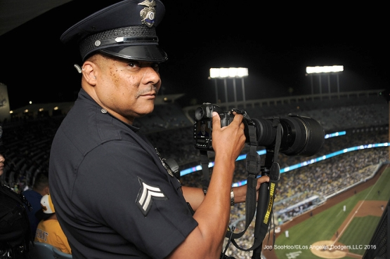 LAPD Officer Don Thompson takes some photos during Los Angeles Dodgers game against the Colorado Rockies Tuesday, June 7, 2016 at Dodger Stadium in Los Angeles,California. Photo by Jon SooHoo/© Los Angeles Dodgers,LLC 2016