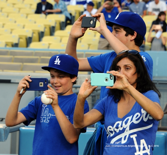 Fans take pictures on the field during pregame ceremonies.
