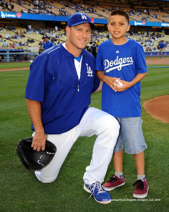A.J. Ellis poses for a photo with ceremonial first pitch participant Luis Garcia during part of the Dodgers Blue Wishes program.