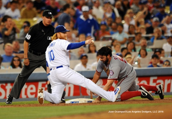 Justin Turner points to Chase Utley after tagging out the Nationals' Tanner Roark at third base in the fifth inning.