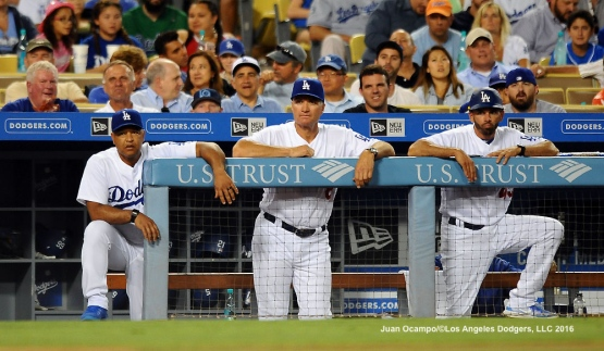 Dodgers manager Dave Roberts and coaches Bob Geren and Chris Woodward, watch from the dugout.