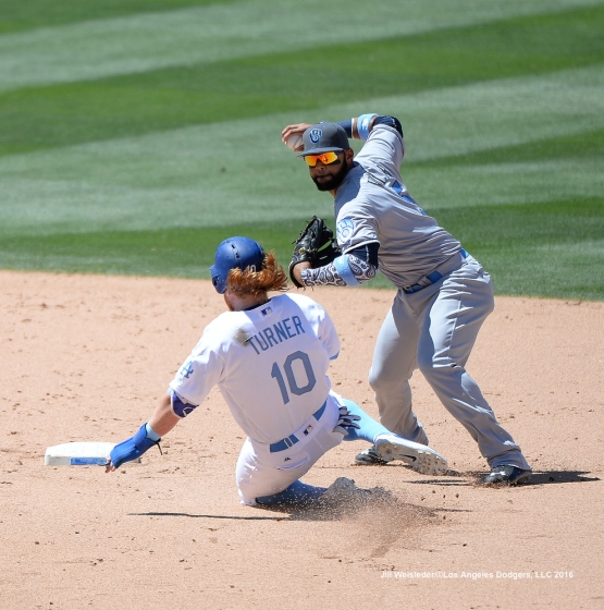 Justin Turner attempts to slide under the glove of Milwaukee Brewers short stop Jonathan Villar. Jill Weisleder/Dodgers