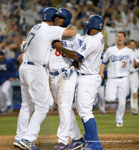 A.J. Ellis and Howie Kendrick hug Yasiel Puig at home plate after scoring the winning run over the Nationals. Jill Weisleder/Dodgers