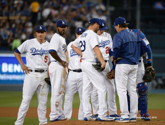 Pitching coach Rick Honeycutt discusses strategy on the mound with pitcher Scott Kazmir. Jill Weisleder/Dodgers