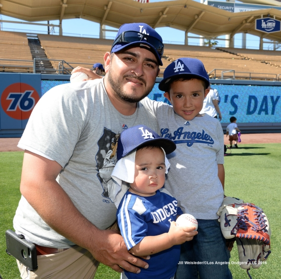 A family poses for a photo post-game on the field for Father's Day catch.  Jill Weisleder/Dodgers