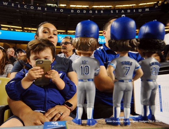 A young fan takes a photo of a bobble-head featuring the tri-MVPs of the 1981 World ChampionshipÑRon Cey, Steve Yeager and Pedro Guerrero.
