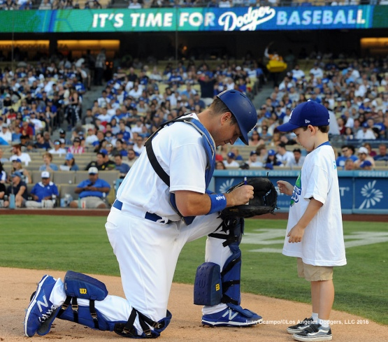 "A.J. Ellis autographs a baseball for ""Kids Taking The Field"" participant."