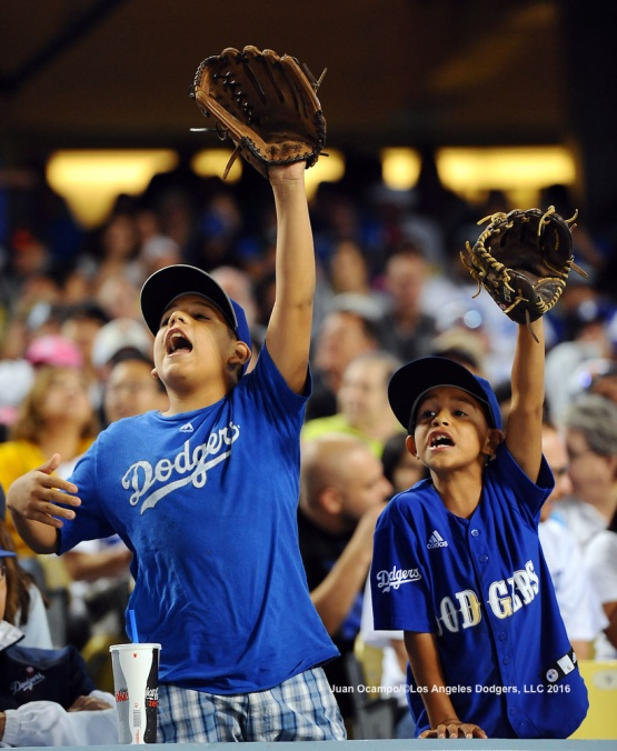Two young fans call out for a baseball.