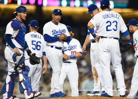 Dodgers manager Dave Roberts visits the mound during a pitching change.
