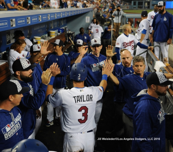 Chris Taylor celebrates in the dugout with the players. Jill Weisleder/Dodgers