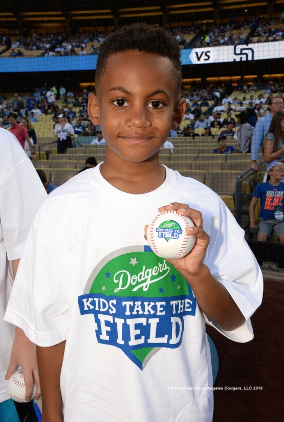 A young Kids Take the Field participant shows off his ball. Jill Weisleder/LA Dodgers