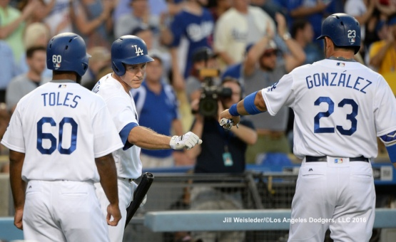 Chase Utley bumps fists with Adrian Gonzalez and Andrew Toles after scoring in runs. Jill Weisleder/Dodgers
