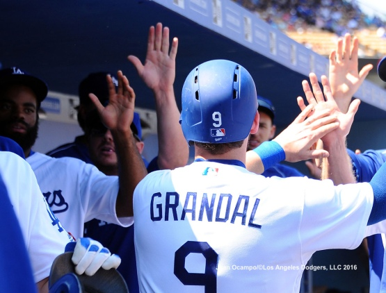 Yasmani Grandal is greeted in the dugout by his teammates after scoring in the fourth inning.
