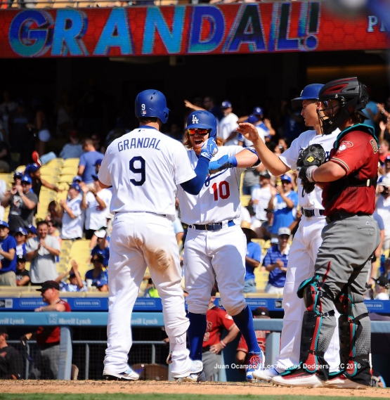 Yasmani Grandal is greeted at home plate by Justin Turner and Corey Seager after his three-run home run.
