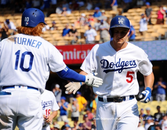 Corey Seager is greeted by Justin Turner after his home run in the seventh inning.