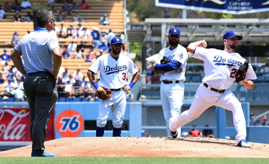 Assistant athletic trainer Nathan Lucero, Chris Taylor and Scott Van Slyke, watch as Bud Norris throws to the plate.