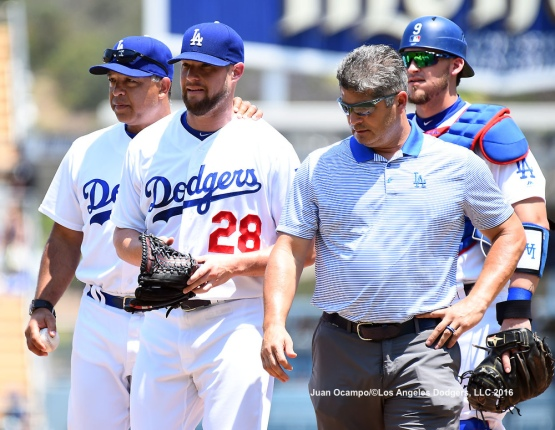 Bud Norris (center) walks back to the dugout with manager Dave Roberts and assistant athletic trainer Nathan Lucero after being removed from the game in the first inning due to muscle tightness.