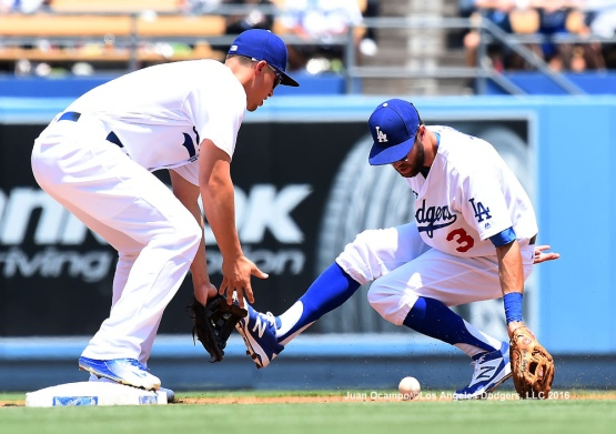 Chris Taylor and Corey Seager make a play on the ground ball during the first inning.
