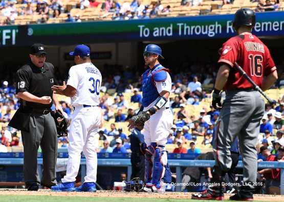 Dave Roberts argues the call of catchers interference by home plate umpire Todd Tichenor as Yasmani Grandal and the Diamondbacks' Chris Owings look on.