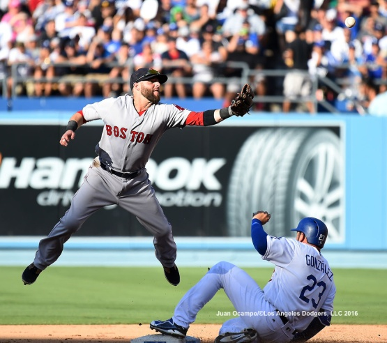 Adrian Gonzalez is safe at second base as the Red Sox's Dustin Pedroia leaps for the ball in the fifth inning.