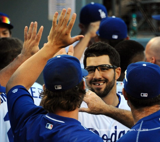 Rob Segedin high-fives his teammates in the dugout after his second two RBI hit of the game.
