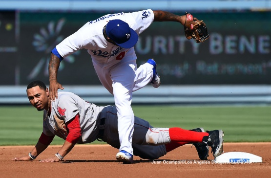 Howie Kendrick leaps over the Red Sox's Mookie Betts at second base in the first inning.
