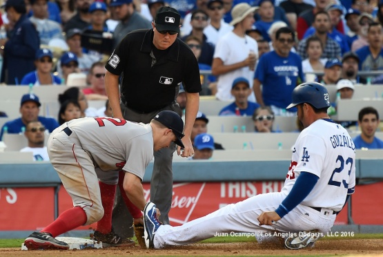 Adrian Gonzalez slides safely into third base on a missed catch error by the Red Sox's Brock Holt in the fourth inning.