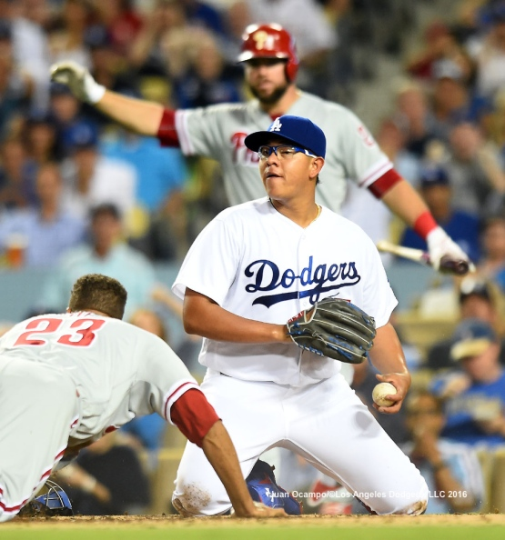 Julio Urias looks to make a play as the Phillies' Aaron Altherr slides in safely to score at home.