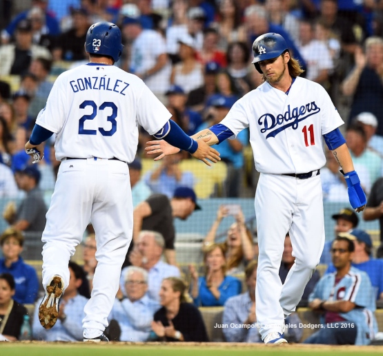 Adrian Gonzalez and Josh Reddick congratulate each other after scoring.