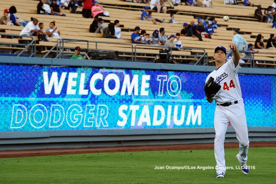 Rich Hill warms up in the outfield before the game.