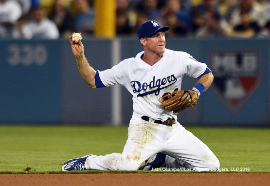 Chase Utley throws from his knees after diving to field a ground ball.