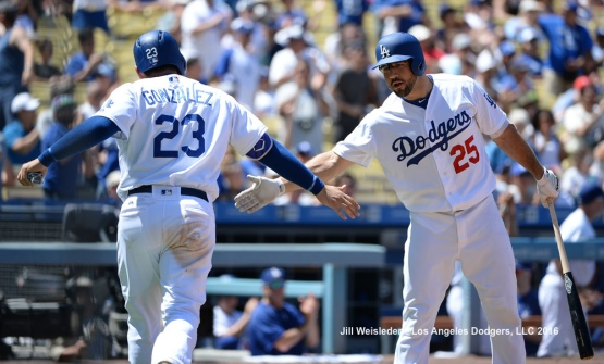 Rob Segedin greets Adrian Gonzalez as he comes in to score. Jill Weisleder/Dodgers