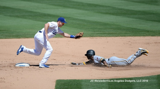 Pittsburgh Pirates Andrew McCutchen slides safely under the glove of Chase Utley . Jill Weisleder/Dodgers
