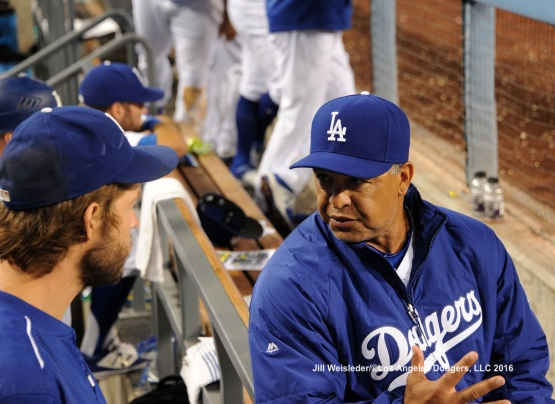 Dave Roberts and Clayton Kershaw speak in the dugout in between innings. Jill Weisleder/Dodgers