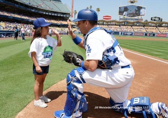A.J. Ellis high-fives a participant during Kids Take the Field. Jill Weisleder/Dodgers