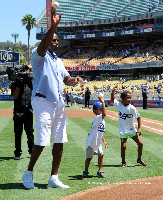 "Earvin ""Magic"" Johnson along with his two grandchildren throw out the ceremonial first pitch prior to the start of the game. Jill Weisleder/Dodgers"