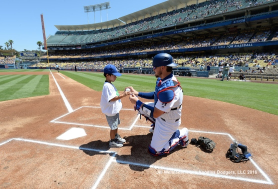 "Yasmani Grandal signs a ball for a young fan during ""Kids Take the Field"". Jill Weisleder/Dodgers"