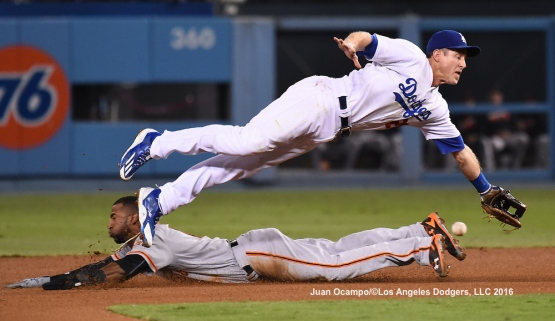 Chase Utley dives for the throw to second base over the Giants' Eduardo Nunez.