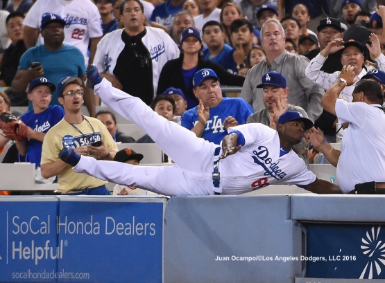 Yasiel Puig dives into the stands attempting to catch a foul ball.