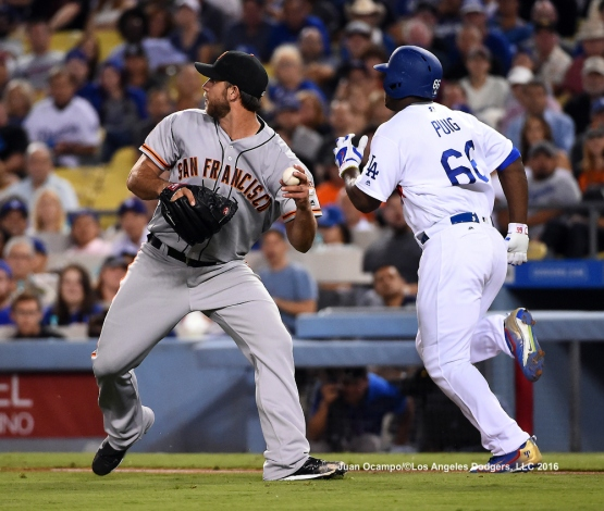 Yasiel Puig runs to first base as the Giants' Madison Bumgarner gets set to make the throw.