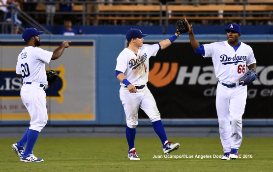 Andrew Toles, Enrique Hernandez and Yasiel Puig celebrate after the game.