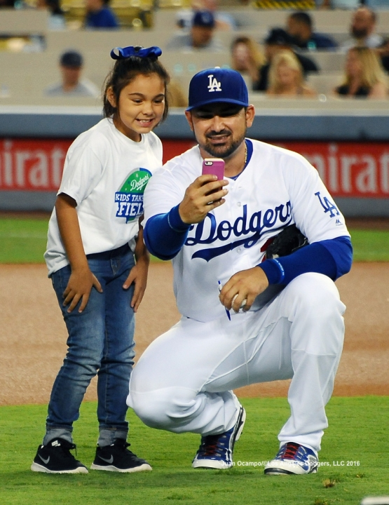 "Adrian Gonzalez takes a photo with a ""Kids Taking the Field"" participant."