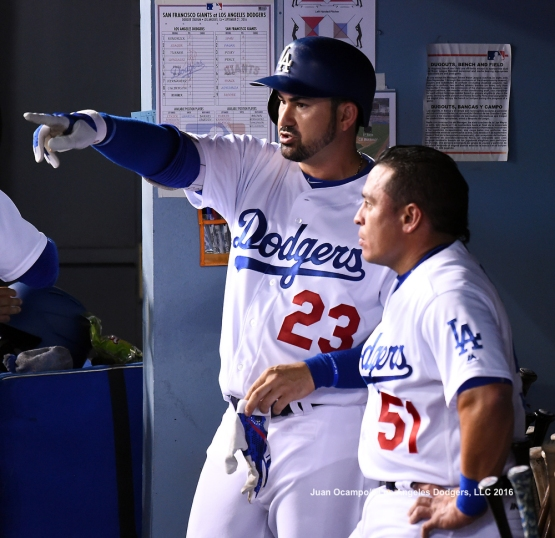 Adrian Gonzalez and Carlos Ruiz talk in the dugout.