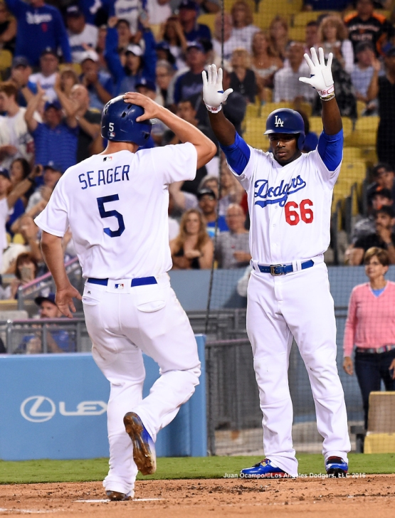 Corey Seager scores and is greeted by Yasiel Puig in the first inning.