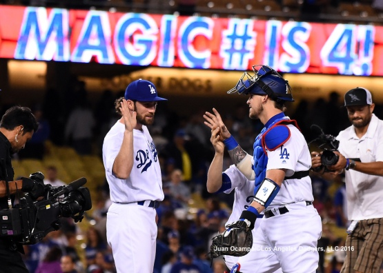 The Dodgers celebrate their 7-4 win over the Rockies and reduce their magic number to four games.