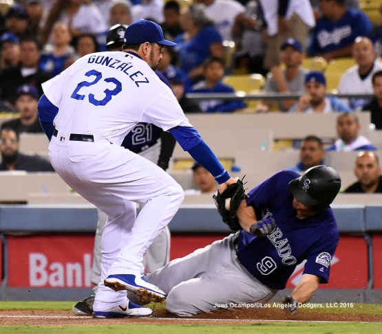 Adrian Gonzalez tags out the Rockies' DJ LeMahieu at first base in the first inning.