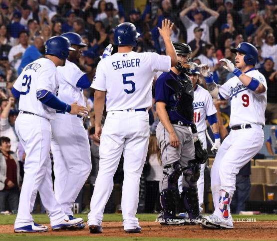 Yasmani Grandal is greeted at home by Yasiel Puig, Adrian Gonazalez and Corey Seager after hitting a grand slam in the seventh inning.